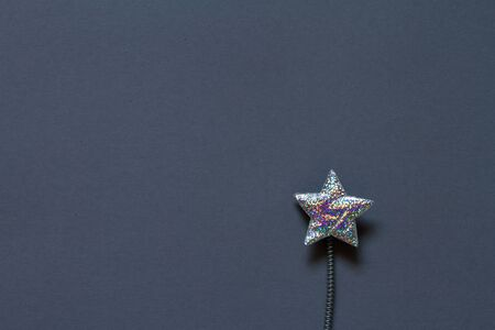 Close up silver glitter plastic star with spring on gray background, minimalistic concept or background