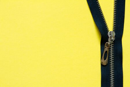 Open zipper clasp with a golden slider on yellow background, minimalistic background or concept
