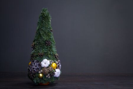 Christmas tree made of fir branches and decorated by natural materials and balls, christmas and New Year minimalistic composition.