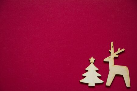 Minimal winter creative table flat lay, wooden figures of Christmas tree and deer on red backdrop