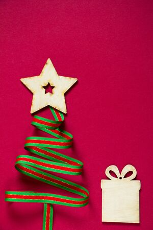 Minimal winter creative table flat lay, Christmas tree made of ribbon and wooden star and gift figurines on a red background