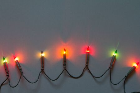 Christmas or New Year background, garland with colorful lights on gray background, selective focus