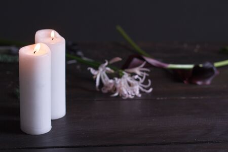 Close up of two large white candles burning on a dark background, selective focus