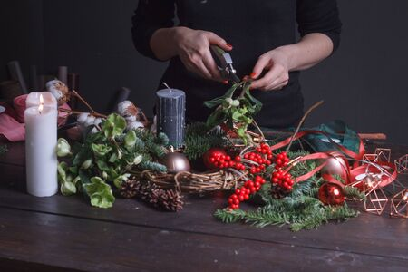 Nahaufnahme einer weiblichen Floristin, die einen Weihnachtskranz aus Tannenzweigen, Weihnachtsblasen und natürlichem Dekor macht, selektiver Fokus