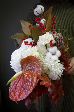 Woman hands holds Christmas or New Year composition bouquet on a dark background, selective focus