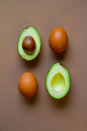 Raw two halves of avocado and brown chicken egg on brown background, creative food concept Reklamní fotografie