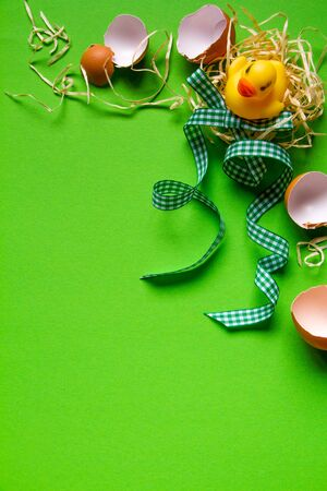 Yellow rubber duck in straw nest, broken eggshell and green checkered ribbon, minimalistic easter background or concept Stock fotó