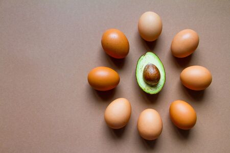 Few brown chicken eggs around a half of ripe avocado, the concept of ketogenic nutrition, the image of the watch dial