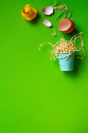 Yellow rubber duck, broken egg shell and miniature bucket with straw, minimalistic easter background or concept Reklamní fotografie - 135503601