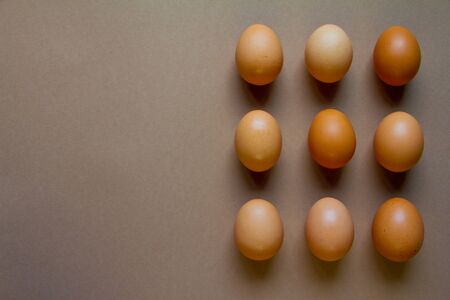 Nine brown chicken eggs on brown backdrop, minimalistic food or easter concept