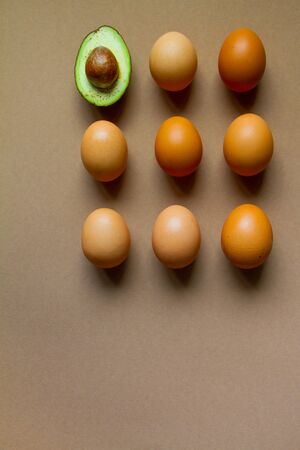 One half of row avocado and few chicken eggs on brown background, flat, top view Reklamní fotografie - 135503756