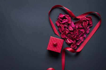 Red petals and silk ribbon shaped in the shape of heart and red gift box on black background, congratulations concept