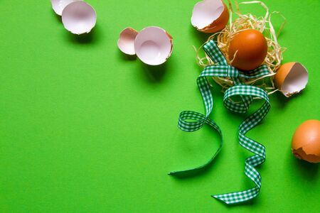 Brown chicken egg in straw nest, broken eggshell and green checkered ribbon, minimalistic easter background or concept