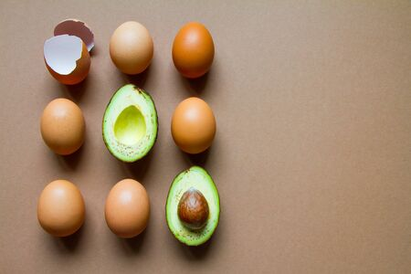 One half of row avocado, few chicken eggs and eggshell on brown background, flat, top view
