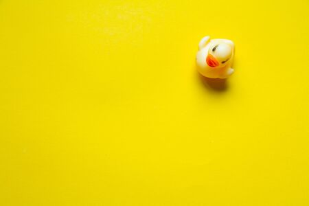 Top view of yellow rubber duck on yellow backdrop, minimalistic concept or background
