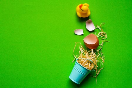 Yellow rubber duck, broken egg shell and miniature bucket with straw, minimalistic easter background or concept Reklamní fotografie
