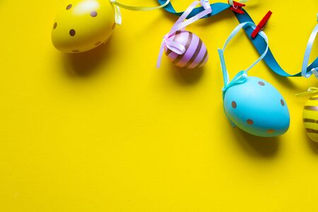 Easter decoration, garland of colored eggs on bright yellow background