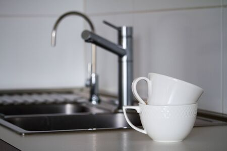 Two clean white tea cups on the background of metal sink with a water tap, faucet and drinking tap, selective focus