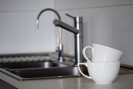 Two clean white tea cups on the background of metal sink with a water tap, faucet and drinking tap, selective focus Stock Photo