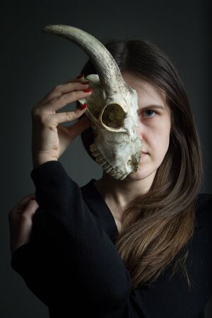 Portrait of young dark-haired girl holding half a goat skull in front of her face, duplicity concept