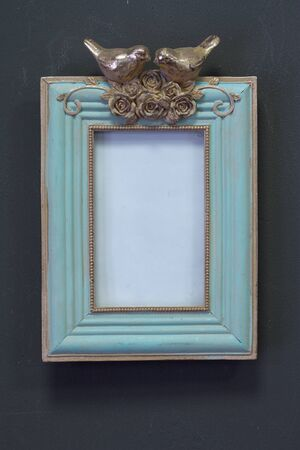 Empty mint golden vintage square frame in Victorian style on gray wall, background or concept