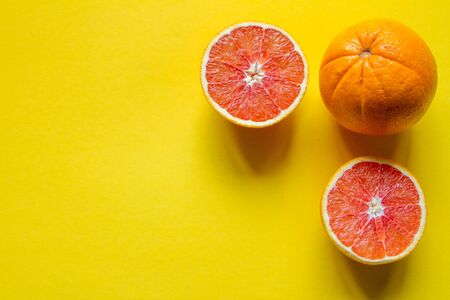 Top view whole and sliced ripe grapefruit and orange on yellow surface, concept of health and vitamins