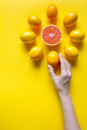 Top view female hand, whole and sliced ripe lemons, grapefruit laid out in the shape of dial on a yellow surface, concept of health and vitamins