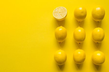 Top view whole and sliced ripe lemon laid out in several rows on yellow surface, concept of health and vitamins 写真素材