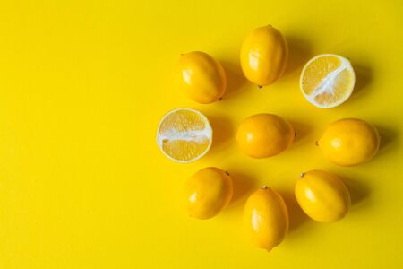 Top view whole and sliced ripe lemons laid out in the shape of dial on a yellow surface, concept of health and vitamins