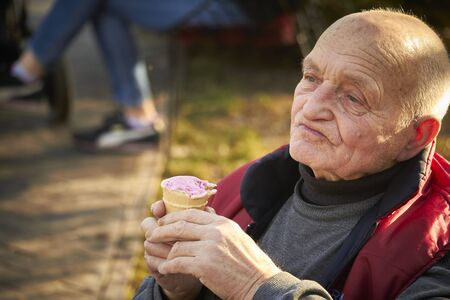 Eighty-year-old man walks in public park, eats ice cream in a waffle cup