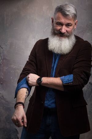 Portrait of a Middle Age Man with Beard and Mustache Posing in Informal Wear on Dark Backdrop, selective focus