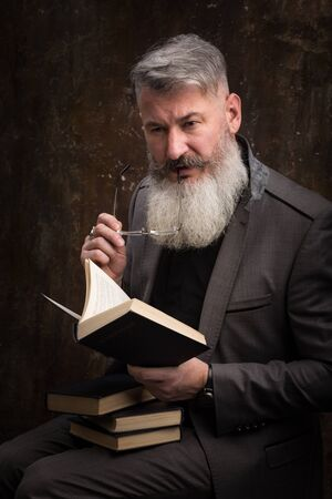 Portrait of a gray haired bearded man with glasses reading book in Russian, on the cover Russian inscription M. Gorky, selective focus