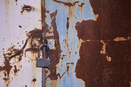 Multicolored backdrop, rusty metal surface with blue paint flaking and metal door with padlock