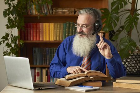 Distance Learning Concept. Teacher professor tutor in headphones teaches discipline online. Mature grey bearded man answers teacher's question through laptop. Stock fotó