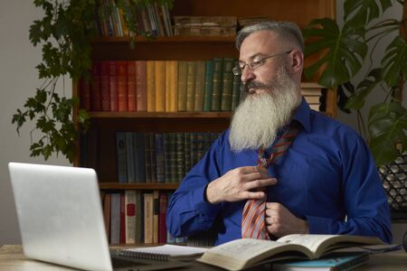 Concept of distance learning. Teacher tutor puts on a tie and prepares for an online lesson. Mature bearded man prepares for online training.