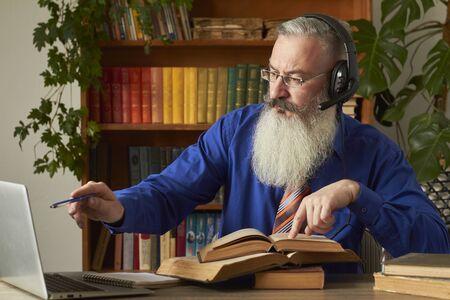Distance Learning Concept. Teacher professor tutor in headphones teaches discipline online. Mature grey bearded man answers teacher's question through laptop.