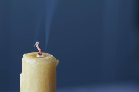 Closeup of an extinct candle and smoke over wick, white candle on blue background, selective focus