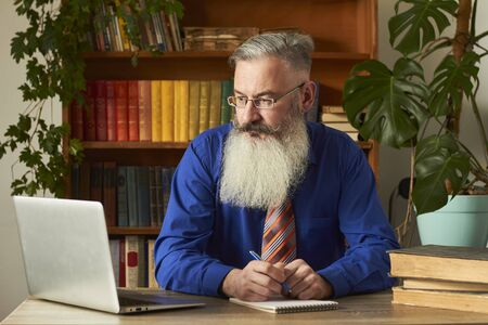 Distance Learning Concept. Teacher professor tutor teaches discipline online. Mature grey bearded man answers teacher's question through laptop. Stock fotó