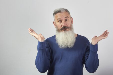 Portrait of perplexed mature gray-haired bearded man on grey background, selective focus