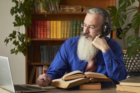 Distance Learning Concept. Teacher professor tutor teaches discipline online. Mature grey bearded man answers teacher's question through laptop.