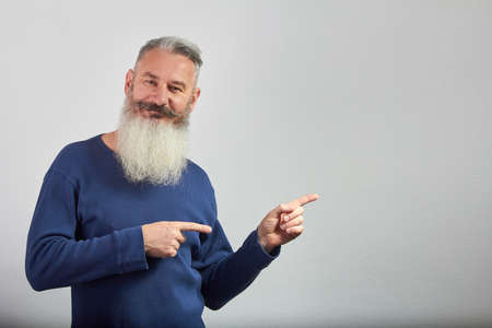 Portrait of mature gray-haired bearded man in blue sweatshirt points forefingers to side on gray backdrop, selective focus 版權商用圖片