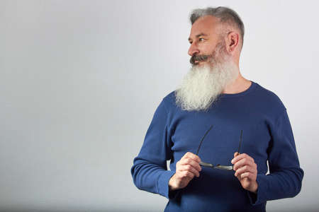 Portrait of mature gray-haired bearded man in blue sweatshirt with eyeglasses in his hand looks away on gray background, selective focus 版權商用圖片