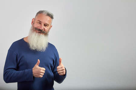 Portrait of mature gray-haired bearded man shows two thumbs up on grey background, selective focus