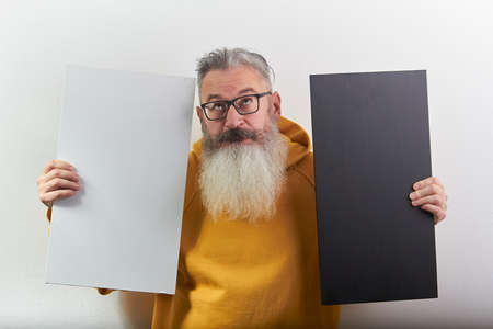 Portrait of mature gray-haired bearded man with white and black sheet over white background, selective focus 版權商用圖片