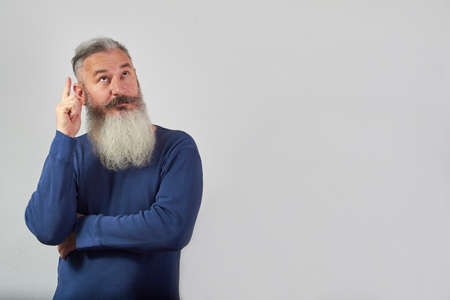 I have an idea concept, portrait of mature gray-haired bearded man on grey background, selective focus