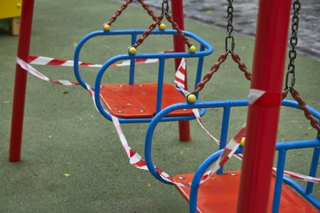 Empty playground without children with striped red and white warning tape, limitations quarantined for Covid19 coronavirus