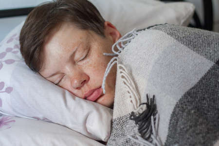 Mature brunette woman sleeping in bed under plaid blanket, concept of illness or cold, treatment at home, selective focus