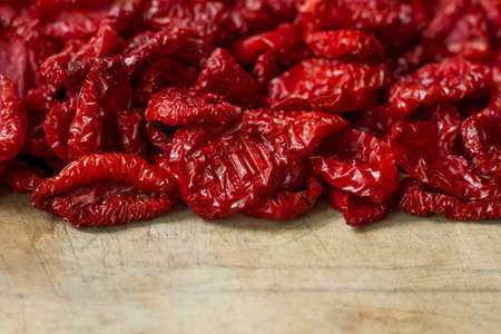 Close up sundried tomatoes with spices and olive oil on wooden cutting board, background or concept, selective focus