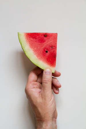 Male hahd holding slice of ripe red watermelon on white background, top view