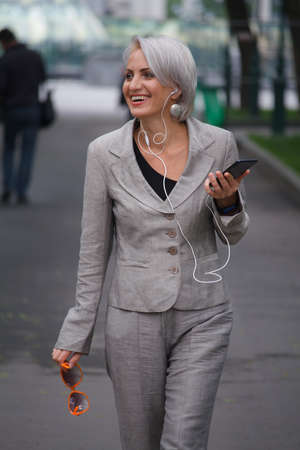 Mature blonde woman in gray suit walks in public park, listens to music with headphones and smiles, selective focus Stok Fotoğraf